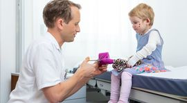 Doctor showing a little girl with epidermolysis bullosa how to do dressings on the childs soft toy