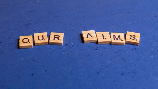 Alphabetic characters on small wooden blocks lying on a blue background, showing the words our aims
